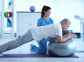 female therapist guiding to the senior man doing a planking