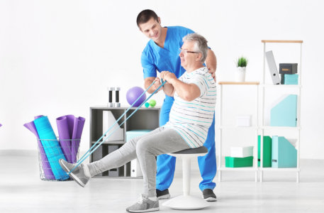 male therapist having a physical therapy session to the senior man